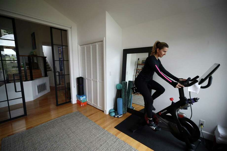 Cari Gundee rides her Peloton exercise bike at her California home. More people are turning to Peloton due to shelter-in-place orders because of the coronavirus (COVID-19). Peloton stock has continued to rise over recent weeks even as most of the stock market has plummeted. Photo: Ezra Shaw, Staff / Getty Images / 2020 Getty Images