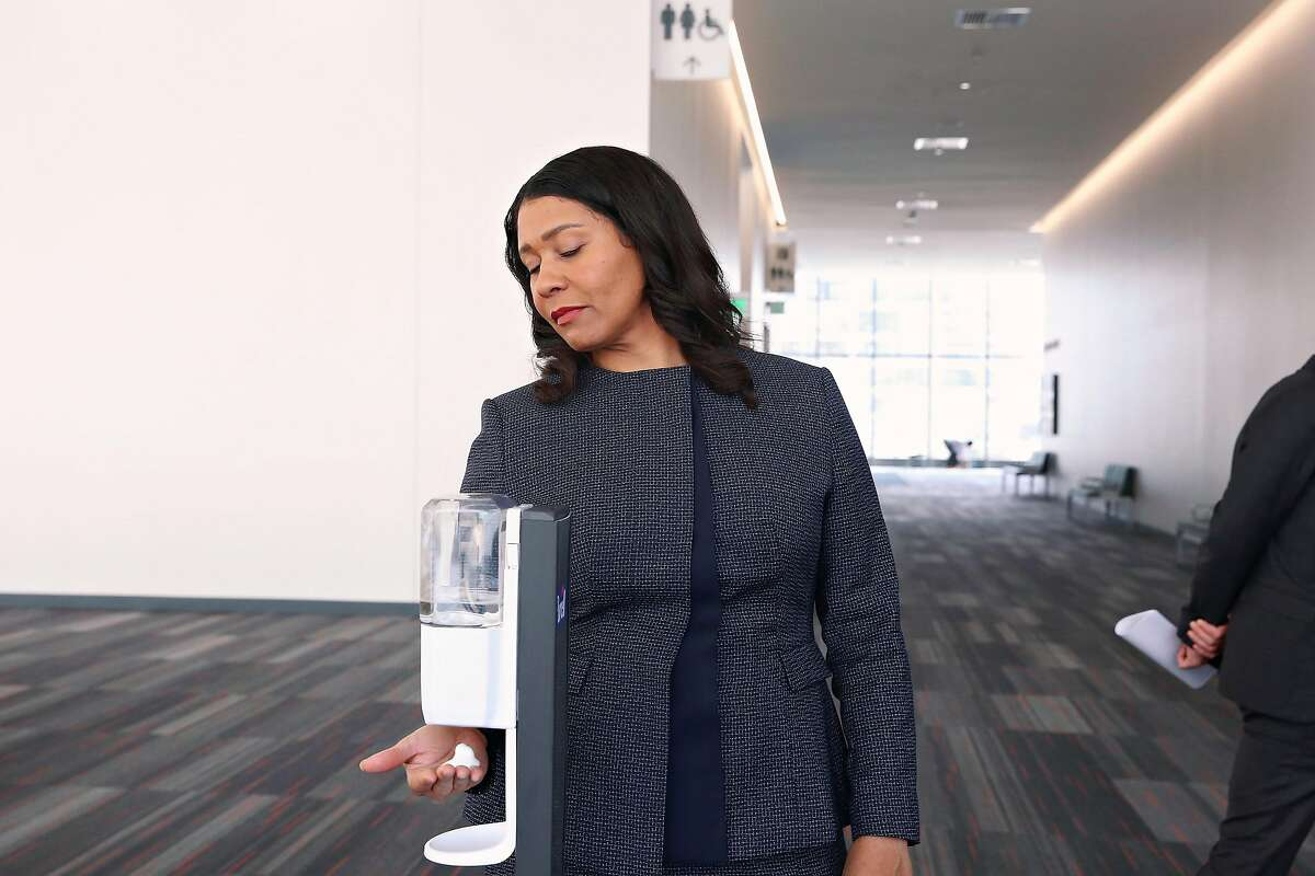 Mayor London Breed gets a spritz of sanitizer from a dispenser while waking through the Emergency Operations Center at Moscone Center on Friday, March 27, 2020 in San Francisco, Calif.