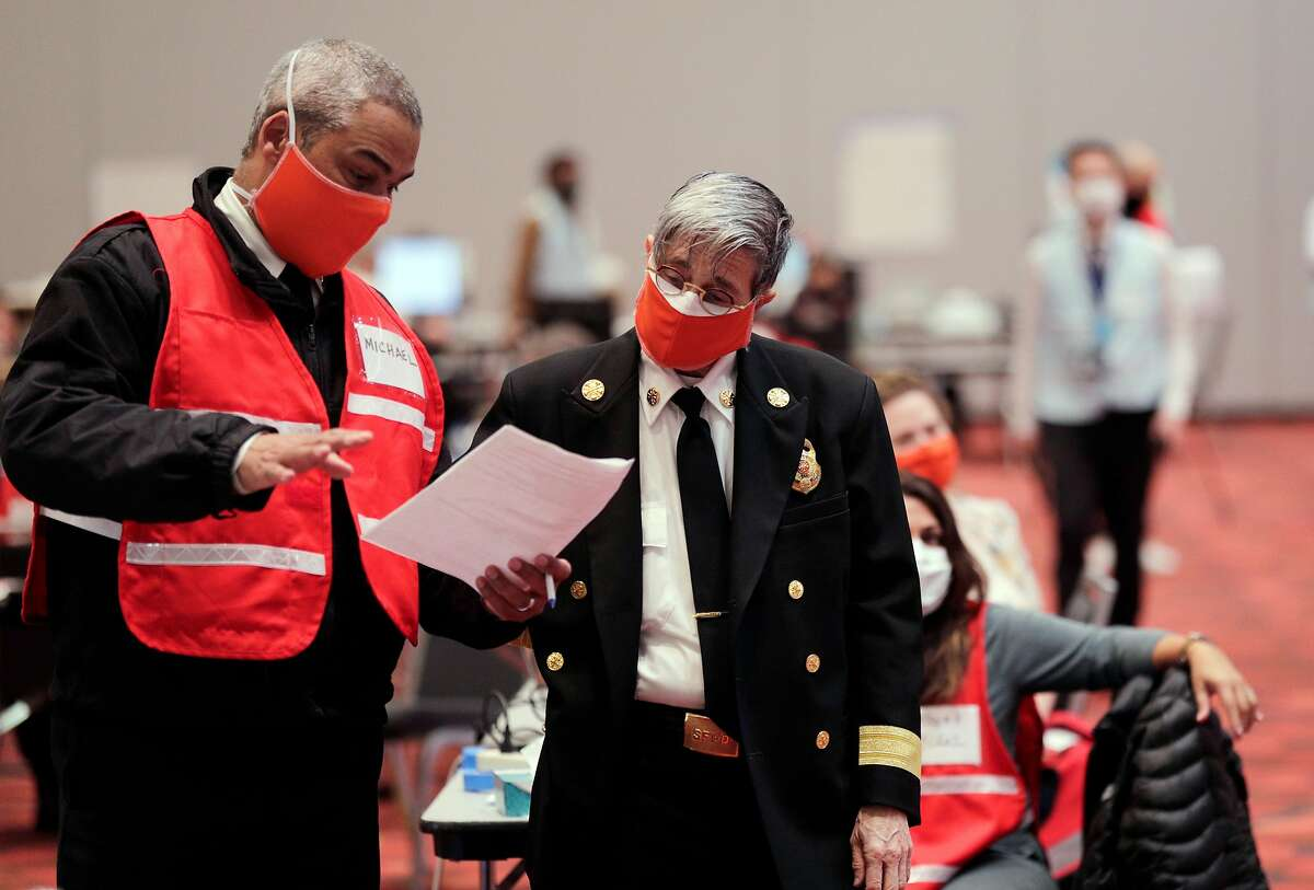 San Francisco Fire Chief, Jeanine Nicholson, right, checks in with Battalion Chief Michael Thompson at George R. Moscone Convention Center South where the Emergency Operations Center for the city has replaced city hall in San Francisco, Calif., on Tuesday, April 21, 2020. It's the closest thing that SF has to a City Hall right now, where wide hallways and massive meeting rooms designed for large crowds instead is very loosely filled with hundreds of city workers involved in battling COVID-19's impact on the city.