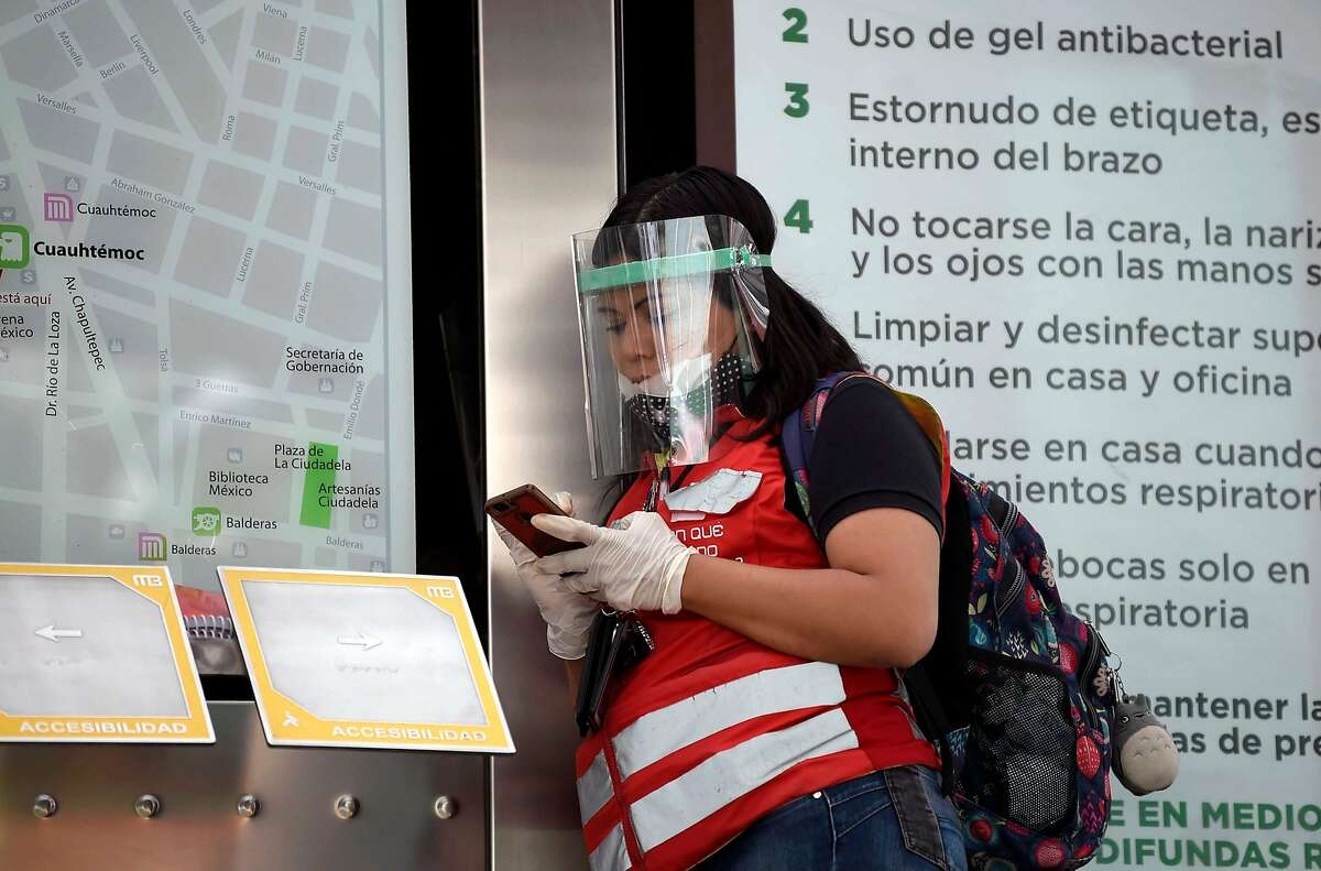 A metro bus worker wearing protective gear due to the COVID-19 coronavirus pandemic, checks her phone in Mexico City, on May 13, 2020. (Photo by ALFREDO ESTRELLA / AFP) (Photo by ALFREDO ESTRELLA/AFP via Getty Images)