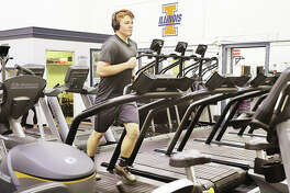 Zach Knight of Godfrey works out Wednesday on a treadmill at Nautilis Fitness Center, 4425 Industrial Drive in Alton, on their first day of its re-opening to the public under guidelines approved by the Madison County Board of Health. Madison County's plan follows a different schedule than that proposed by Gov. J.B. Pritzker, leaving businesses concerned about legal and insurance ramifications.
