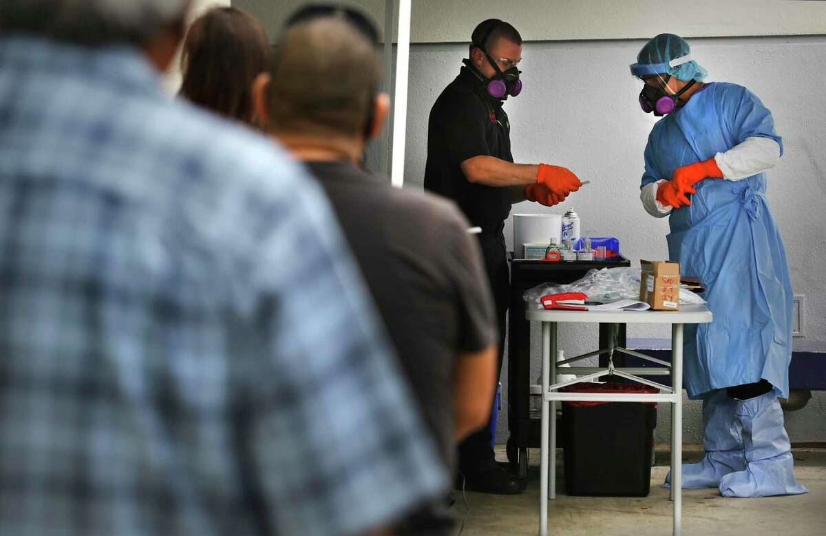 San Antonio firefighters check information as they perform COVID-19 testing at Las Palmas Public Library on Thursday, May 7, 2020.