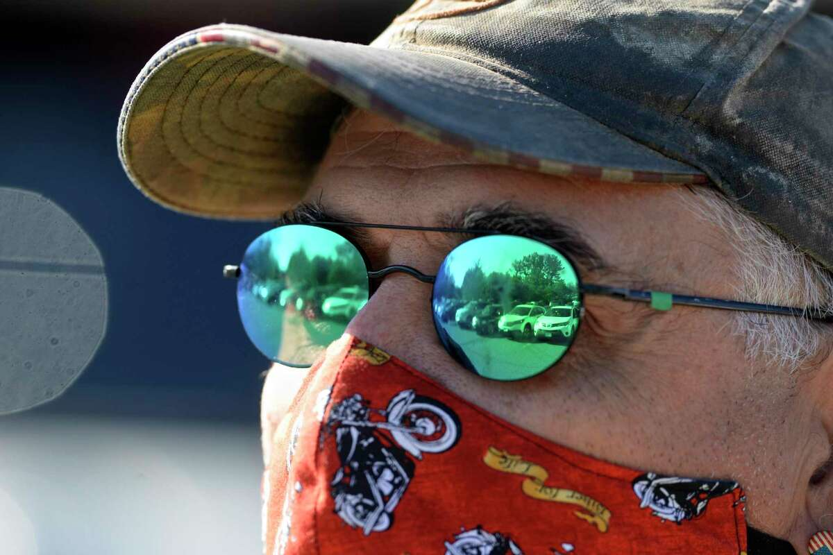 A line of cars is reflected in Bill McArdle's sunglasses on Wednesday. He was a volunteer at Walnut Hill Community Church, which gave food to 470 families on Wednesday.