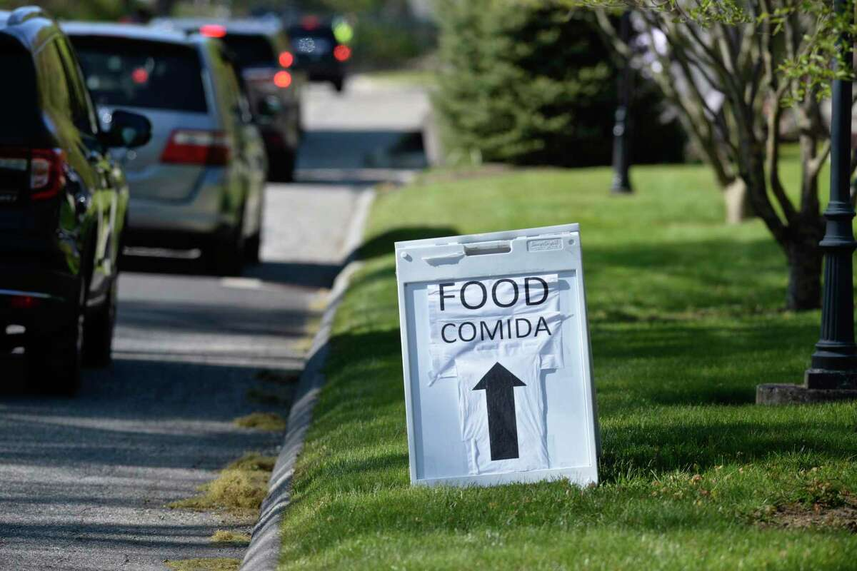 Cars enter Walnut Hill Community Church, in Bethel, Conn, on Wednesday evening. The church distributes food every Wednesday. People show up hours early with food distribution starting at 5:30 PM. Wednesday, May 13, 2020.