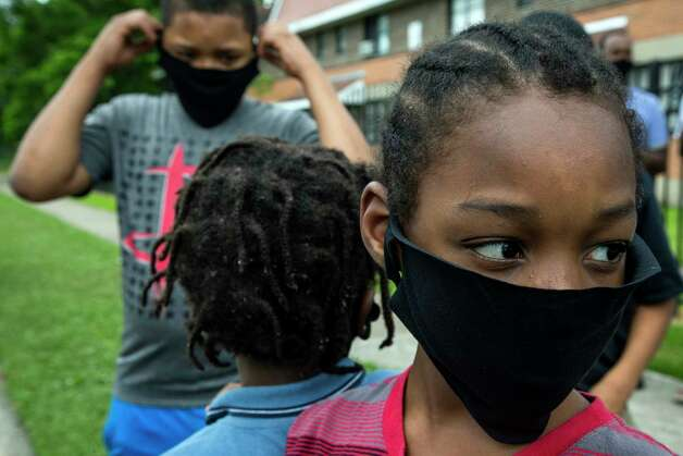 """Jamaurei Jackson dons a mask given to him by rap artist Trae The Truth in the Third Ward on Wednesday, May 13, 2020 in Houston. The rapper spent the day handing out 10,000 masks to people in neighborhoods all around the city. """"I am trying to get masks to people who wouldn't normally be able to get one,"""" he said. Photo: Brett Coomer, Staff Photographer / © 2020 Houston Chronicle"""