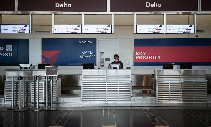 A Delta airlines employee waits for passengers at an empty check-in counter in Ronald Reagan Washington National Airport in Arlington, Virginia, on May 12, 2020. - The airline industry has been hit hard by the COVID-19 pandemic, with the number of people flying having decreased by more than 90 percent since the beginning of March. (Photo by ANDREW CABALLERO-REYNOLDS / AFP) (Photo by ANDREW CABALLERO-REYNOLDS/AFP via Getty Images)