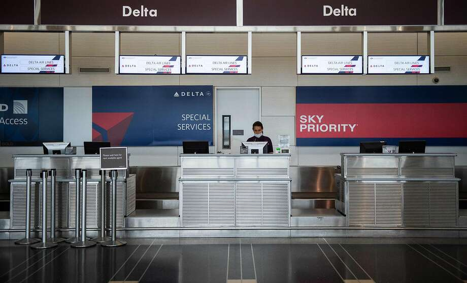A Delta airlines employee waits for passengers at an empty check-in counter in Ronald Reagan Washington National Airport in Arlington, Virginia, on May 12, 2020. - The airline industry has been hit hard by the COVID-19 pandemic, with the number of people flying having decreased by more than 90 percent since the beginning of March. (Photo by ANDREW CABALLERO-REYNOLDS / AFP) (Photo by ANDREW CABALLERO-REYNOLDS/AFP via Getty Images) Photo: Andrew Caballero-reynolds, AFP Via Getty Images