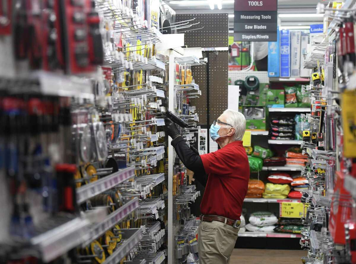 Store employee Joe Biase scans items at Feinsod ACE Hardware in Old Greenwich, Conn. Wednesday, May 13, 2020. Feinsod Hardware and other local hardware stores have been deemed essential businesses and have stayed open throughout the coronavirus outbreak.