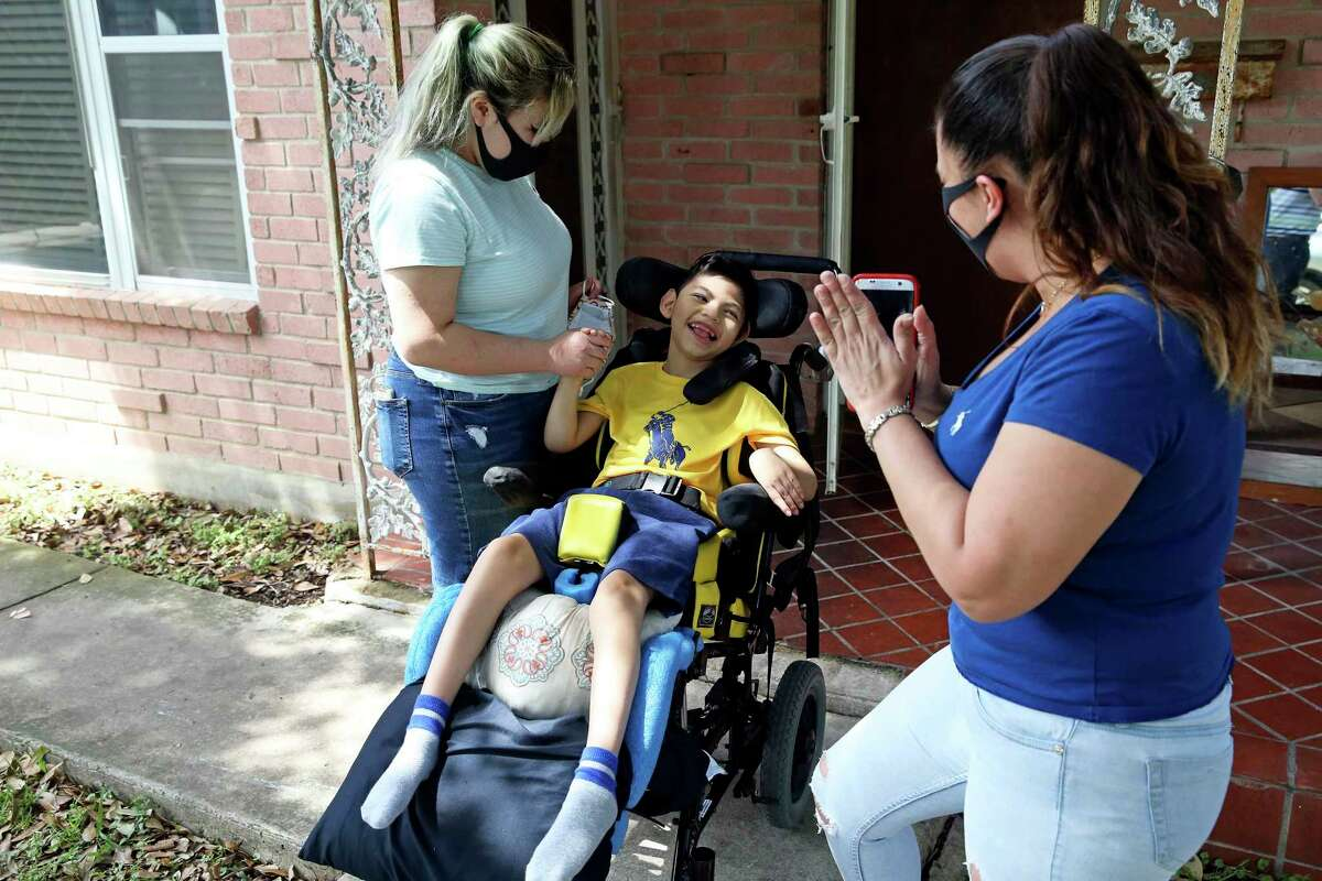 Jayden Arispe, 7, is excited as he waits with his mother, Juanita Cortez, left, and his sister, Gia, before his new wheelchair arrives from Project Mend on May 8, 2020.