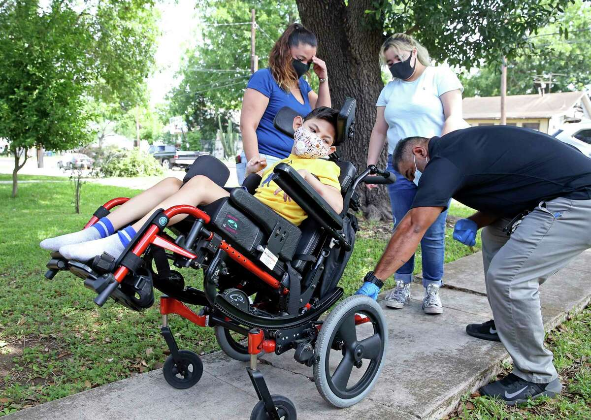 Freddie Zapata of Project Mend adjusts 7-year-old Jayden Arispe's new wheelchair as Jayden, his mom Juanita Cortez, left, and Cortez's daughter Gia watch May 8, 2020. Zapata delivered the new equipment and helped Arispe get settled in.