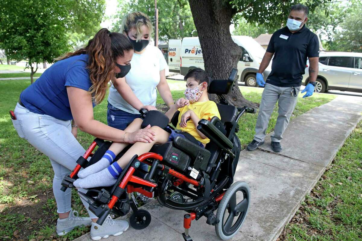 Juanita Cortez, in blue, checks to see that her son, 7-year-old Jayden Arispe is comfortable in the new wheelchair he just received from Project Mend on May 8, 2020, as his sister Gia and Freddie Zapata, distribution and logistics manager of the nonprofit, look on.