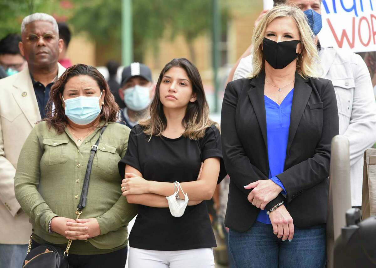 Small business owners, Ana Isabel Castro-Garcia, Stephanie Mata and Shelley Luther listen to the speakers at a freedom rally protesting decisions to shutdown businesses amid the COVID-19 coronavirus pandemic, Wednesday, May 13, 2020, at Laredo City Hall.