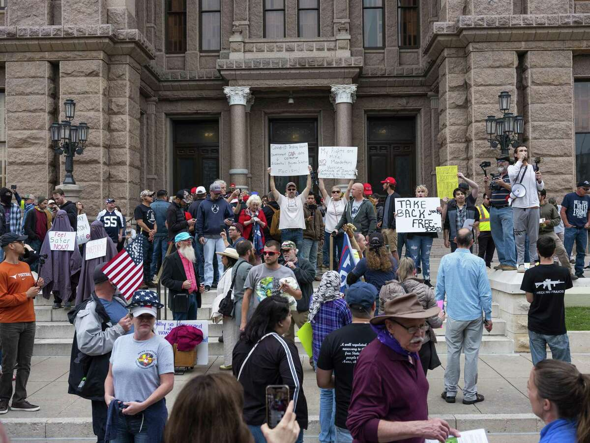"""Demonstrators hold signs while gathering during a """"You Can't Close America"""" rally outside the Texas State Capitol in Austin on Saturday, April 18, 2020. Protesters gathered at the State Capitol Saturday to call for the reopening of the state amid the coronavirus pandemic."""