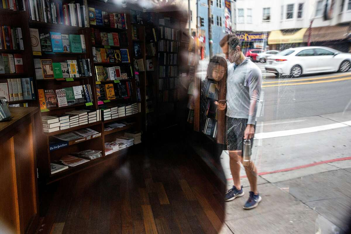 Joy Xu and David Brablec outside City Lights Bookstore on Saturday, March 28, 2020, in San Francisco, Calif. The store is closed during the coronavirus pandemic.