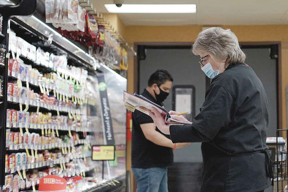 An employee wears a mask and gloves to protect against coronavirus as she checks products Wednesday at a grocery store in Mount Prospect. Photo: Nam Y. Huh | AP
