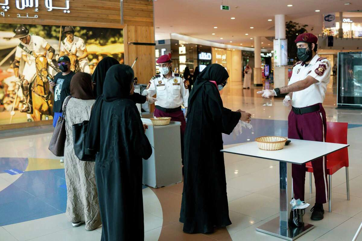 Guards take the temperature of people entering a mall in Riyadh, Saudi Arabia, on May 12, 2020.