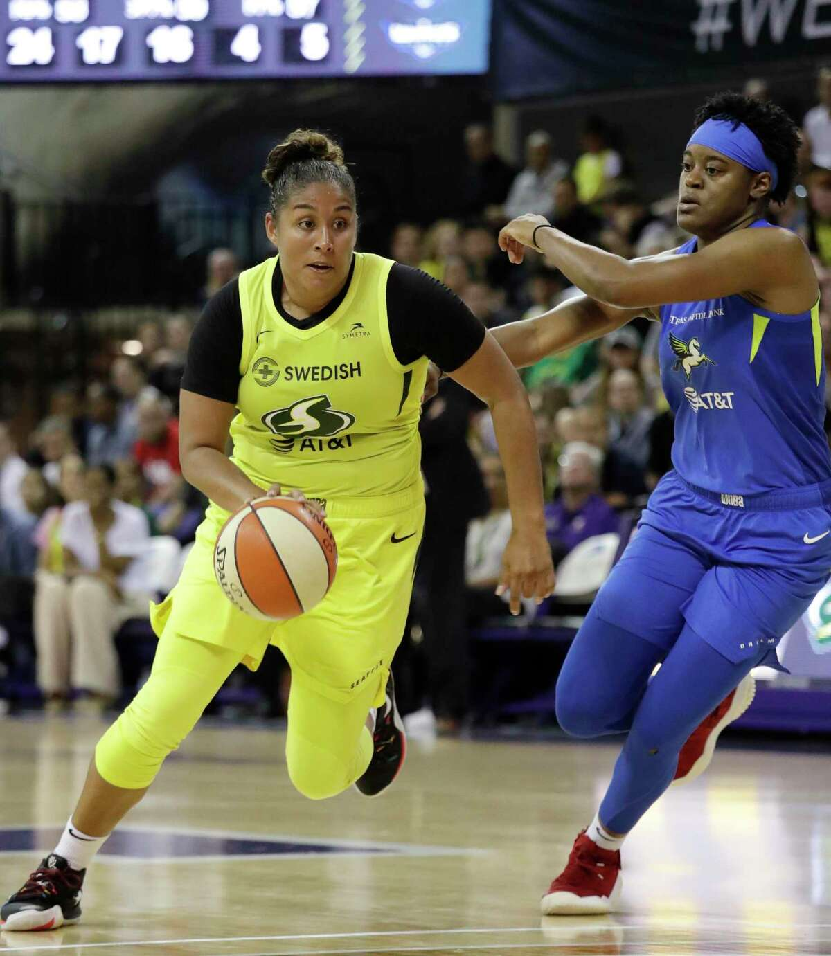 Seattle Storm's Kaleena Mosqueda-Lewis, left, drives past Dallas Wings' Kaela Davis during the second half of a WNBA basketball game Friday, July 12, 2019, in Seattle. Mosqueda-Lewis led the Storm with 18 points in their 95-81 victory.
