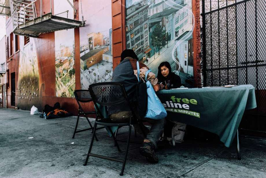"""A San Francisco resident in 2015 learns about the Lifeline program, which offers free phones, minutes and broadband to people receiving benefits like disability or food stamps. A phone can do amazing things, """"when you do have it,"""" said a service provider. Photo: James Martin"""