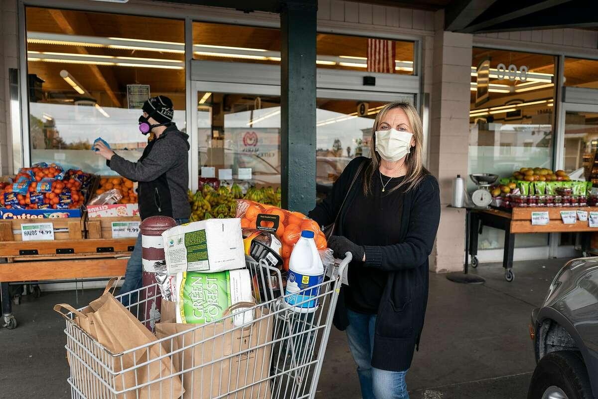 Joanie Blechel, 62, gets groceries wearing a mask at Fircrest Market in Sebastopol, California on April 17, 2020.