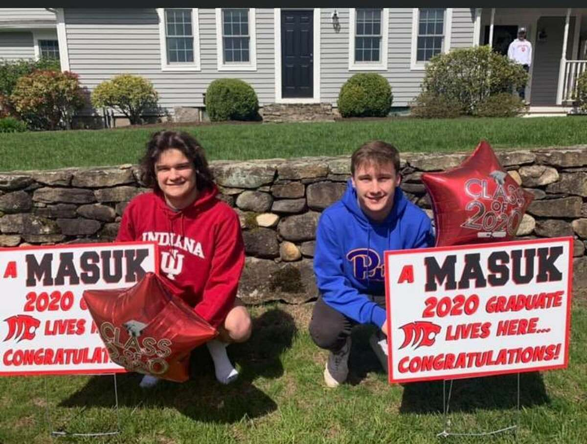 Ethan and Will Briand with their graduation signs on Saturday, May 9.