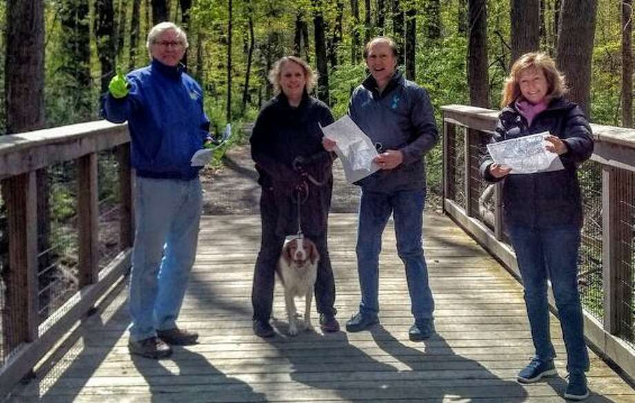 From left, Charlie Taney, president of the Friends of the Norwalk River Valley Trail; Norma and Cliff Fox; and Pat Sesto, former NRVT board president, look at plans for extending the trail from Skunk Lane to Pimpewaug Road in Wilton. Photo: Norwalk River Valley Trail / Contributed Photo / Wilton Bulletin Contributed