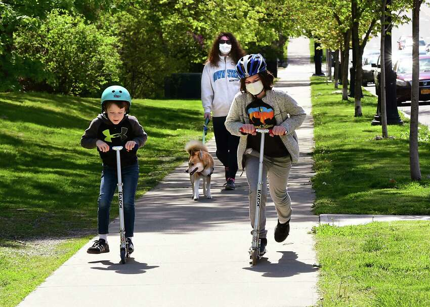 Rose Mitchell of Albany, center, is seen walking her dog Foxy as her sons Caleb Tenerowicz, 6, left, and Rowan Tenerowicz, 10, ride their scooters during an outing along Madison Ave. on Thursday, May 14, 2020 in Albany, N.Y. (Lori Van Buren/Times Union)