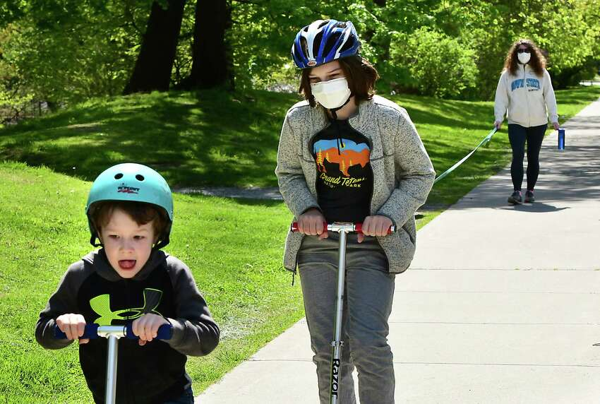 Rose Mitchell of Albany, right, is seen walking her dog Foxy as her sons Caleb Tenerowicz, 6, left, and Rowan Tenerowicz, 10, ride their scooters during an outing along Madison Ave. on Thursday, May 14, 2020 in Albany, N.Y. (Lori Van Buren/Times Union)