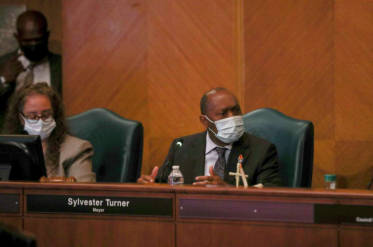 Houston Mayor Sylvester Turner, center, speaks during a City Council meeting in May, before City Hall went virtual due to the COVID-19 pandemic..