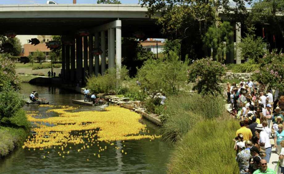 Rubber ducks float down the river near the Interstate 35 overpass during the River Walk Lucky Duck Race & Festival.