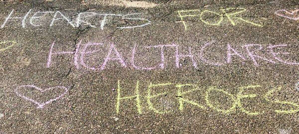 Middletown police and fire department personnel stopped by the Connecticut Department of Children and Families Solnit South center Wednesday to cheer on health-care workers dealing with the COVID-19 pandemic. Youth chalked messages to workers on roadways at the facility.