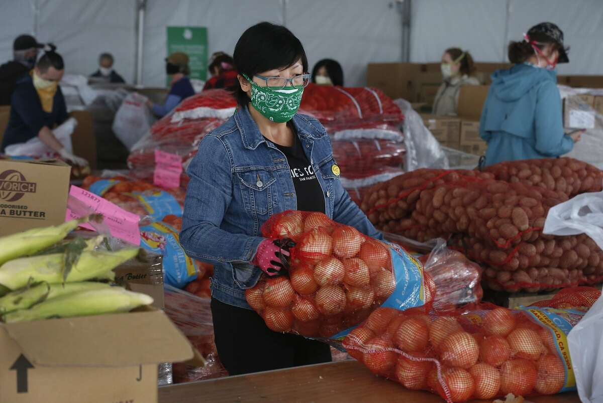Jen Woo, a librarian from the West Portal branch, sorts onions on her volunteer shift at the SF-Marin Food Bank during the coronavirus pandemic in San Francisco, Calif. on Wednesday, May 13, 2020.