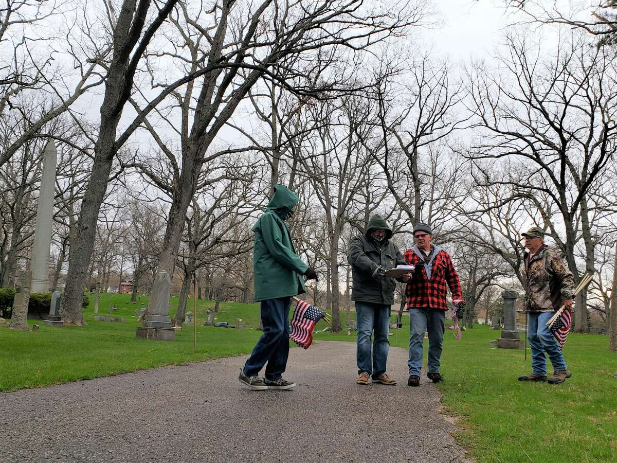 Volunteers search for veterans' gravestones to place a flag next to Thursday morningat Oak grove Cemetery inManistee.