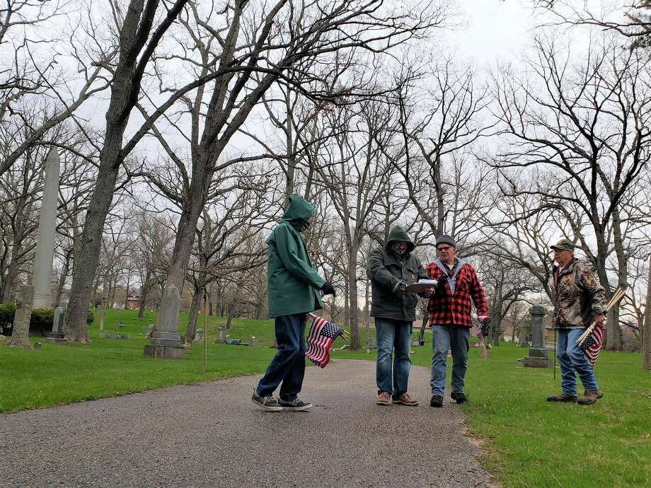Volunteers search for veterans' gravestones to place a flag next to Thursday morning at Oak grove Cemetery in Manistee. Photo: Arielle Breen/News Advocate