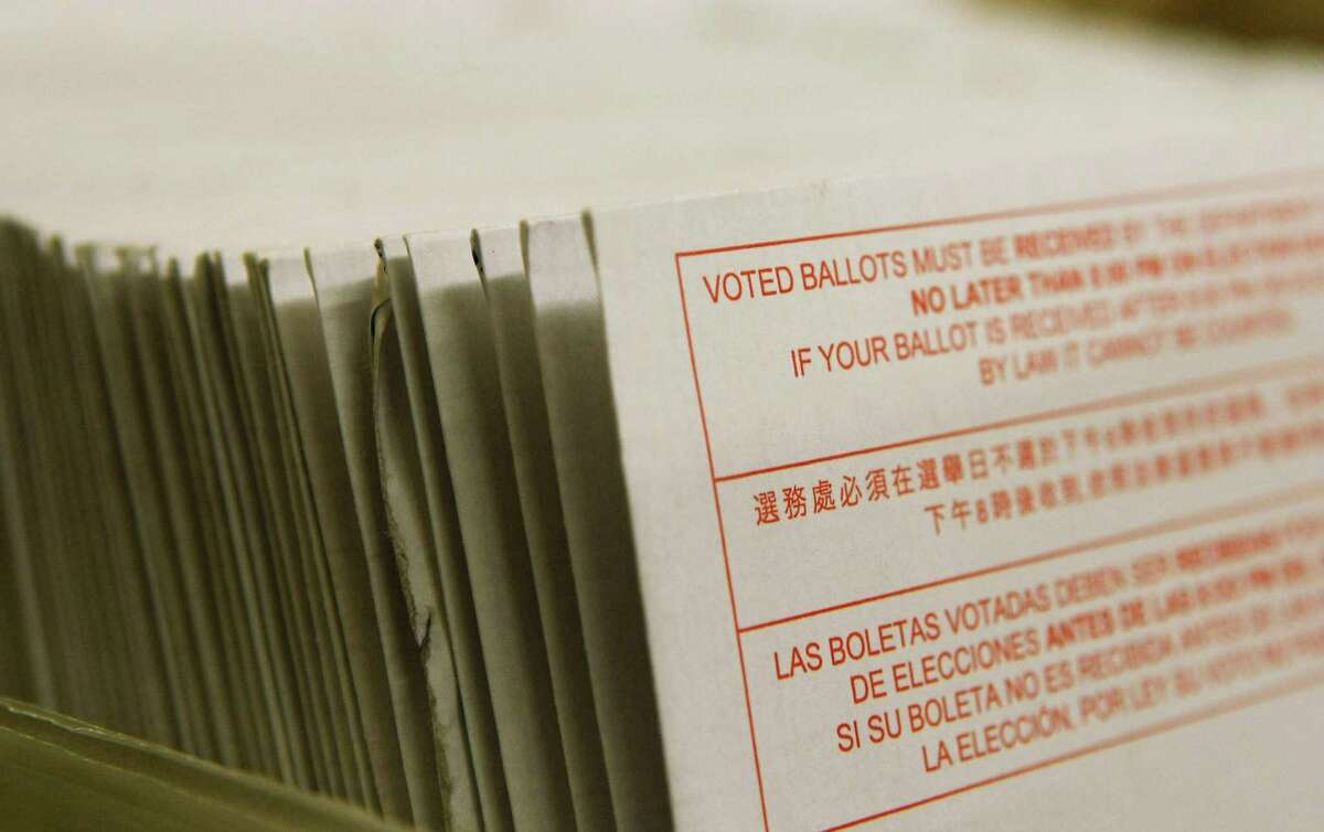A stack of vote-by-mail ballots sit in a box. (Justin Sullivan/Getty Images/TNS)