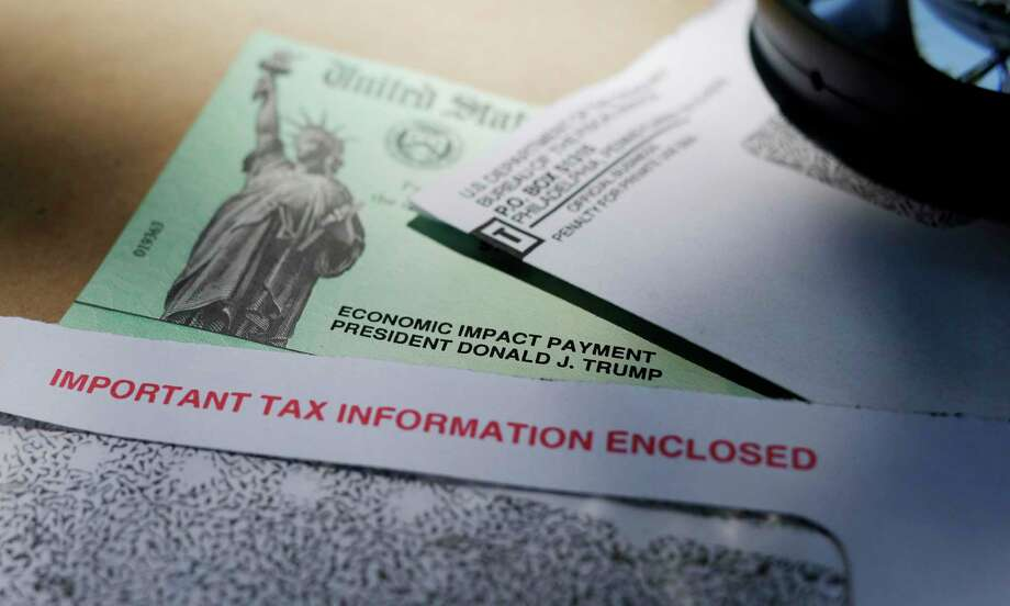In this April 23, 2020, file photo, President Donald Trump's name is seen on a stimulus check issued by the IRS to help combat the adverse economic effects of the COVID-19 outbreak, in San Antonio. President Donald Trump, Treasury Secretary Steven Mnuchin and now the IRS are urging people who received coronavirus relief payments for a deceased taxpayer to return the money to the government. But legal experts say there is no law requiring people do that. (AP Photo/Eric Gay, File) Photo: Eric Gay, STF / Associated Press / Copyright 2020 The Associated Press. All rights reserved.