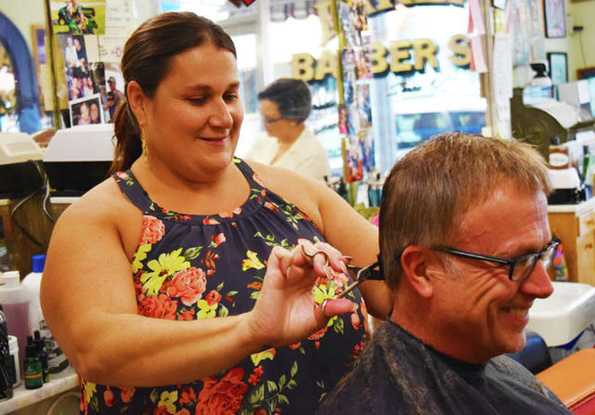 In this October 2019 file photo, third-generation owner of Eaker's Family Barber Shop, Kari Eaker-Overholtz, gives her client a trim. Eaker's, 227 N. Main St., Edwardsville, will remain closed for now to protect the business' license and stay clear of fines from the state.