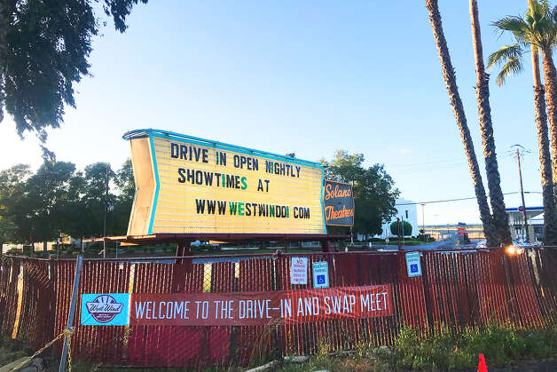 """Nationwide, drive-in theaters are having an unexpected, anachronistic moment. Since their late-1950s heyday when 4,000 were in operation across the U.S., their numbers have been decimated. Now there are only about 300 left. But the state of California allowed the few drive-in movies left to reopen in early May, despite the ongoing lockdown. The Bay Area has two of them — this West Wind Solano location in Concord and its sister venue in San Jose — and both have to operate under strict guidelines. Visitors must stay in their cars unless they need to use the restroom, over by the shuttered snack counter between the two screens. Only a few people can be in the restroom (wearing cloth masks) at a given time, and vehicles must be parked 10 feet apart. To ensure that last rule, employees painted throughout the expansive pavement to guide guests to find a spot. """"You need to park right over the orange-painted line,"""" the ticket attendant explained when we arrived. """"Or green line — we ran out of the orange."""" Photo: Alyssa Pereira / SFGATE"""