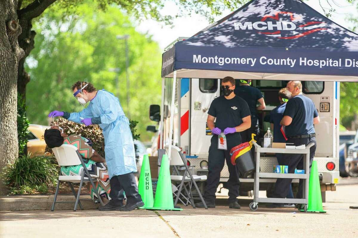 Paramedics with the Montgomery County Hospital District administer tests for COVID-19 outside of an elderly care facility, Thursday, May 14, 2020, at Focused Care at Beechnut in Houston.