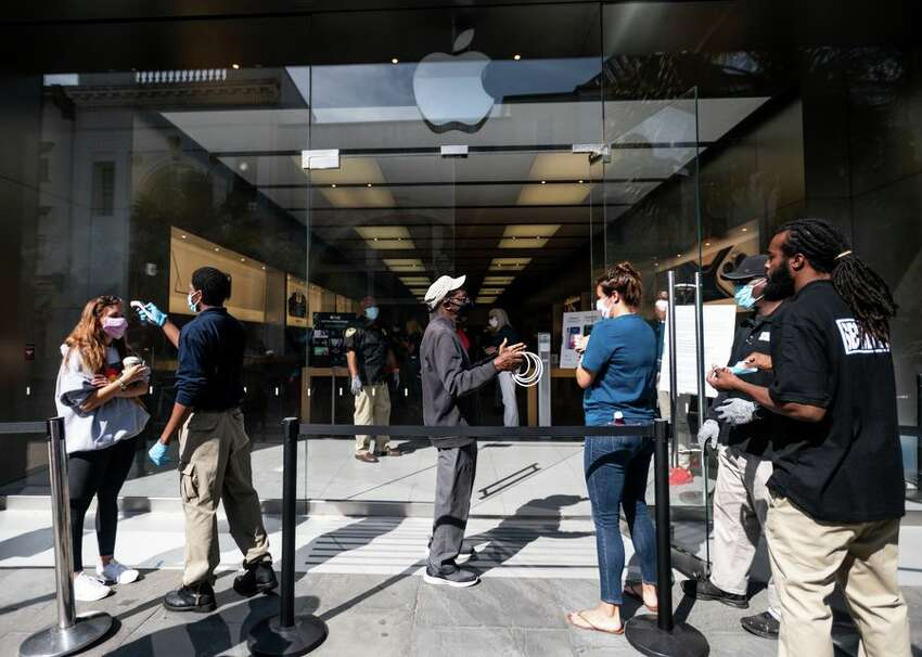 On May 13 in Charleston, South Carolina, Apple store workers and security guards prepare customers to enter the reopened store. Visitors now have to have their temperatures taken and wear masks in the store. Apple is also reopening some stores in Florida, California, Washington, Hawaii, Oklahoma, Colorado and around the world.