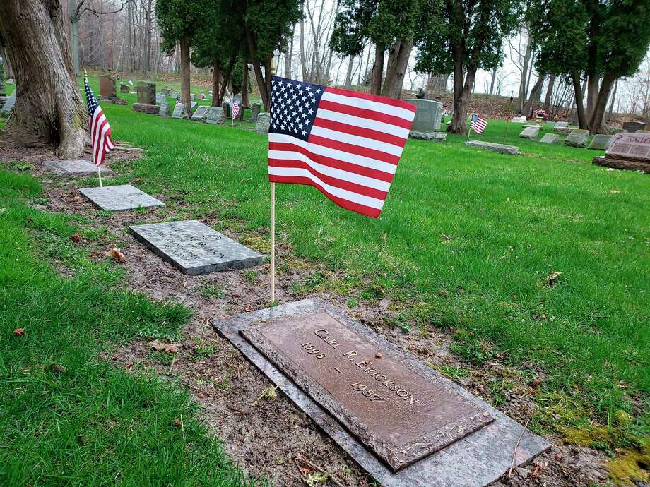 Volunteers placed flags at veterans' grave sites Thursday morning at Oak Grove Cemetery. (Arielle Breen/News Advocate)
