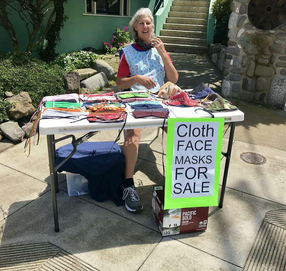 Eileen Purcell of Reno sells homemade face masks on street corner in Sunnyside neighborhood of San Francisco