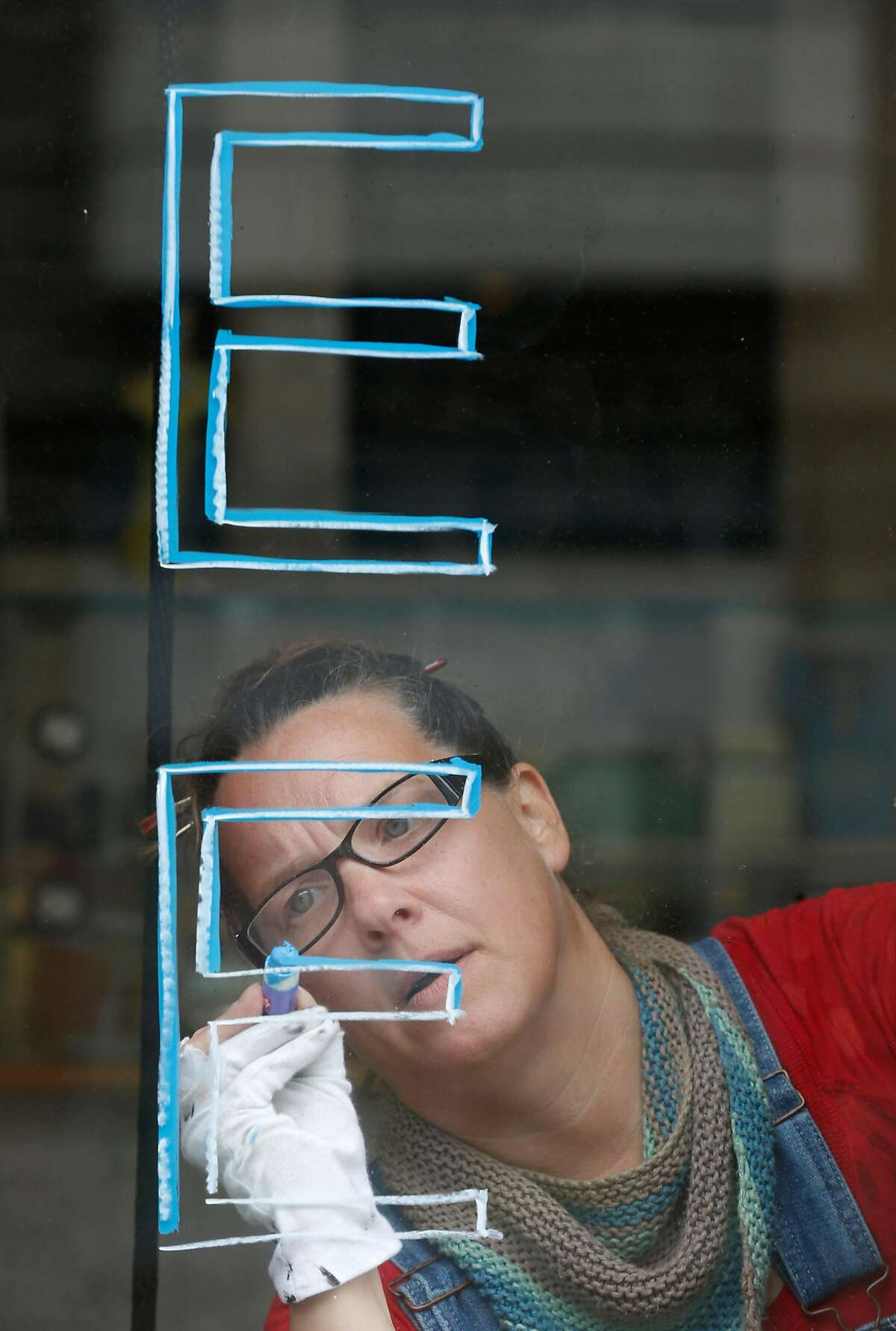 Sign painter Libby Staub applies lettering to the window of Altalena Vinoteca in San Francisco, Calif. on Thursday, May 14, 2020. Staub is angry that Veritas, manager of more than 250 apartment buildings in the city, including hers, received 3.6 million in PPP relief funds form the federal government but she has yet to receive hers.