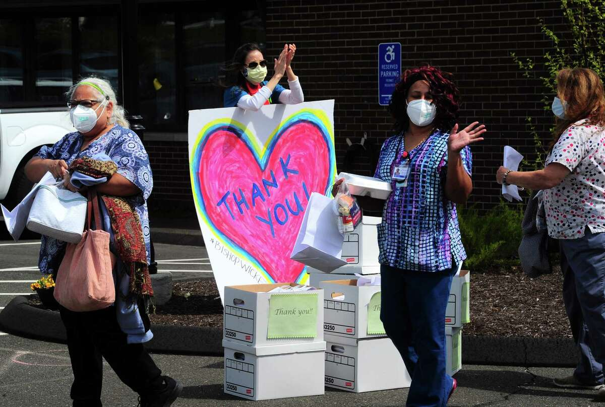 Marissa Salvesen, with United Methodist Homes, in background, claps as health care workers pass by during the change-of-shift at Bishop Wicke nursing home on Long Hill Ave in Shelton, Conn., on Thursday May 14, 2020. The cheer line was established by the Greater Valley Chamber of Commerce in Shelton. About 30 volunteers and administrators from U.N.H. came out to honor the staff at the nursing home.
