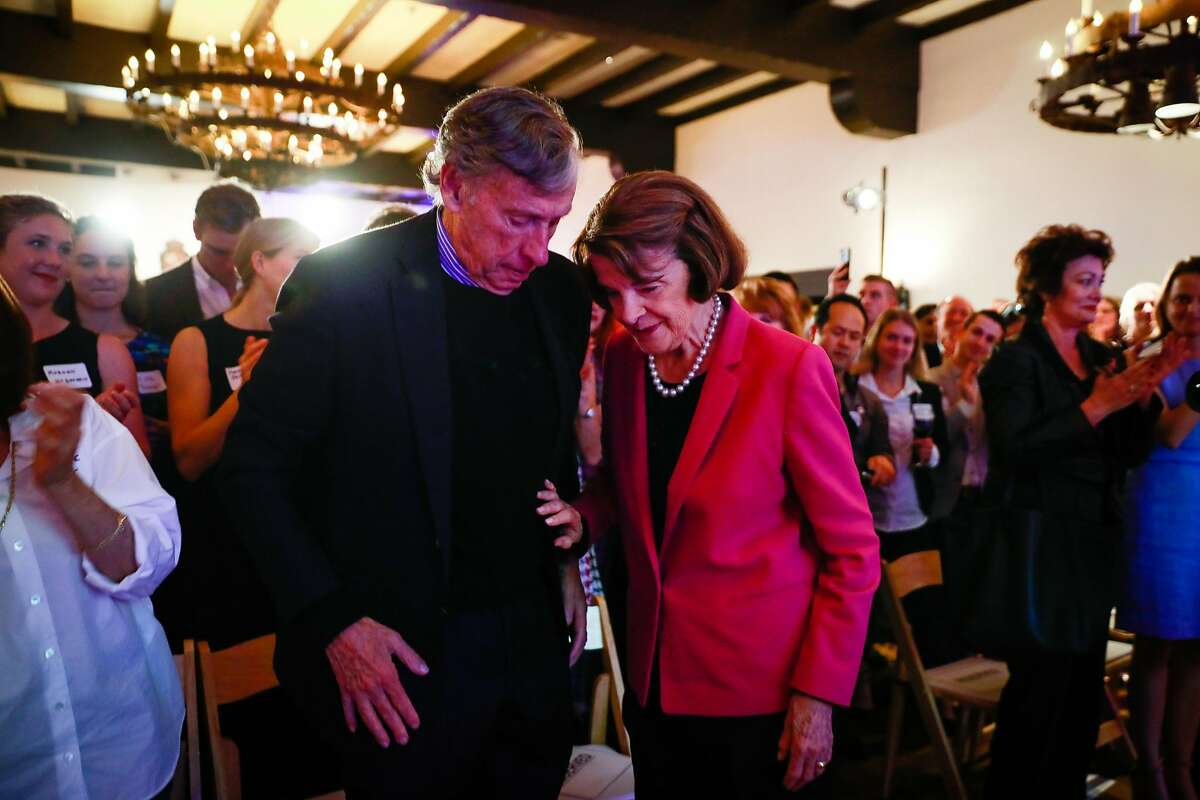 Senator Dianne Feinstein is embraced by her husband Richard Blum (left) after being re-elected for Senator at the Presidio Officers Club in San Francisco, California, on Tuesday, Nov. 6, 2018.