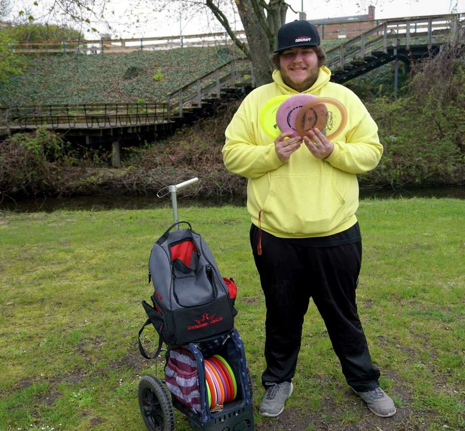 Longtime Big Rapids resident and avid disc-golfer Tony Daniels shows of his growing collection of disc-related gear. (Pioneer photo/Joe Judd)