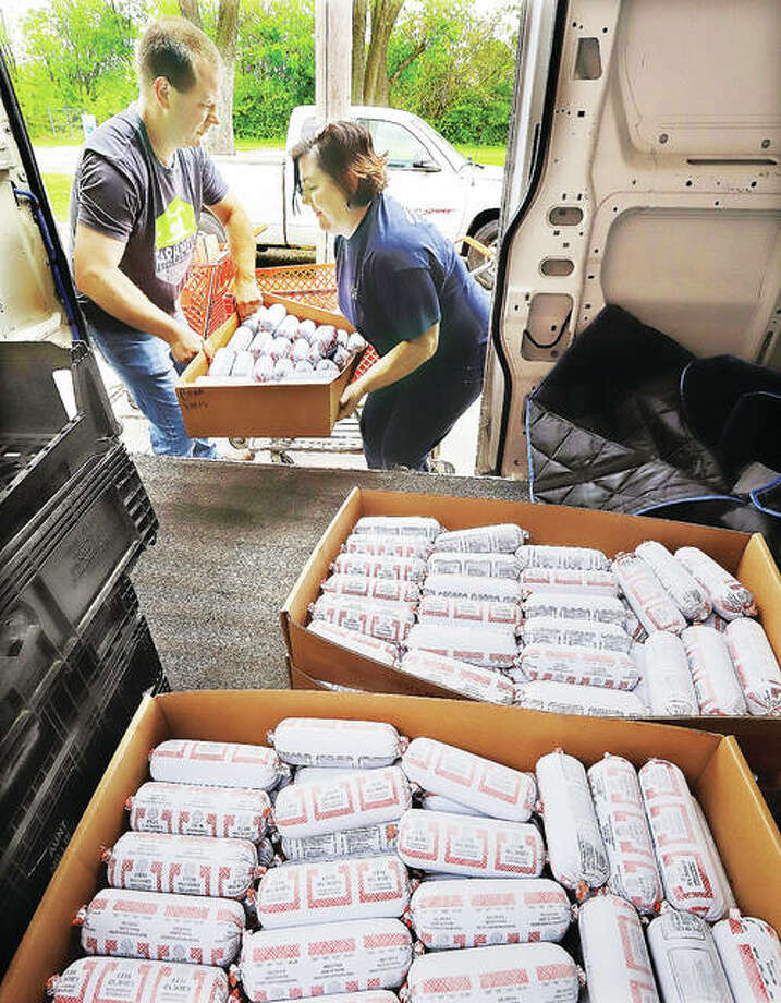 Brian Werts and Denise Ukena unload locally produced ground beef Thursday at the Hope Community Center in Cottage Hills. Farm-Meat LLC, which connects farmers directly to consumers wanting to purchase meat, delivered about 600 pounds of ground beef to the center.