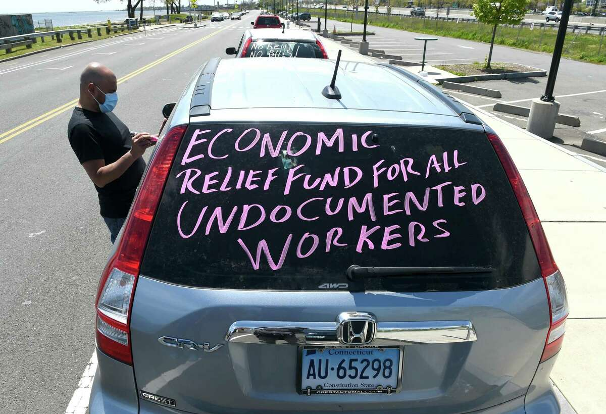 Jhon Molino, of New Haven, writes messages on the window of a car on Long Wharf Drive in New Haven that is part of a car rally that headed to Hartford on Thursday to demand a bailout and disaster relief for immigrant workers.