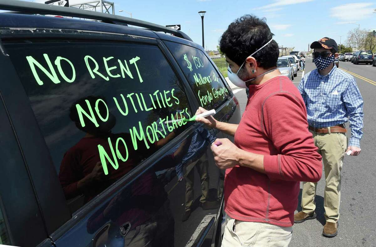 John Lugo of Unidad Latina en Accion writes messages on the window of a car that is part of a car rally on Long Wharf Drive in New Haven that is headed to Hartford on May 14, 2020 to demand a bailout and disaster relief for immigrant workers.
