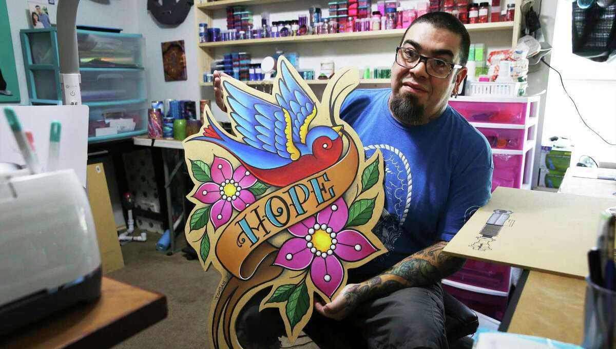 Tattoo artist Jason Casas shows off a giant woodcut he created at his home in San Antonio. Casas has turned to making other art to make ends meet since he cannot tattoo due to COVID-19 restrictions in Texas.
