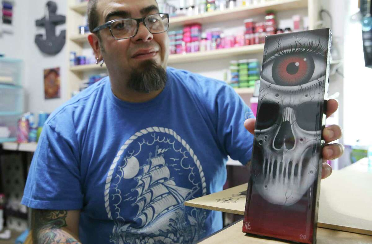 Tattoo artist Jason Casas shows one of his larger works of art on Thursday, May 14, 2020. Casas had to switch canvases from skin to paper, wood, etc. to make a living. Casas has been a local tattoo artist for 16 years and had to close his tattoo parlor due to COVID-19 restrictions. Now he makes woodcut magnets and acrylic paintings.